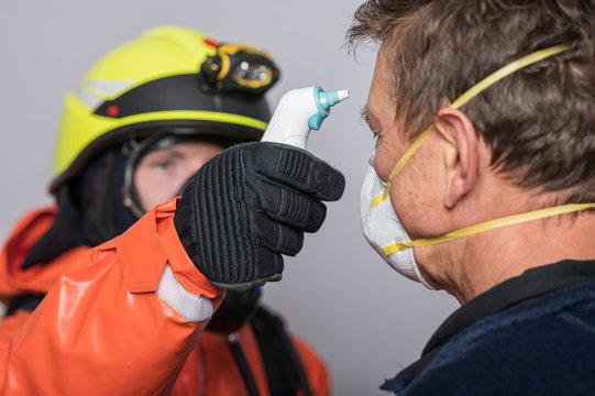 Corona Virus Pandemie ist ausgebrochen. Feuerwehrleute in Seuchenschutzausrüstung und medizinische Helfer messen Fieber bei Personen, um die Epedemie einzudämmen