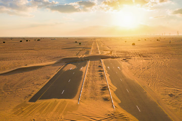 Aerial view of half desert road or street with sand dune in Dubai City, United Arab Emirates or UAE. Natural landscape background at sunset time. Famous tourist attraction. Top view.