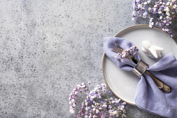 Easter table setting with grey plate and violet flowers, decor on grey stone table. Top view. Space for text