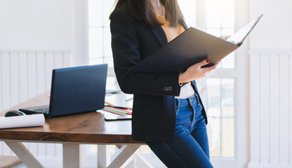 Young asian woman wearing casual suit with jean. she reading document while  working in office