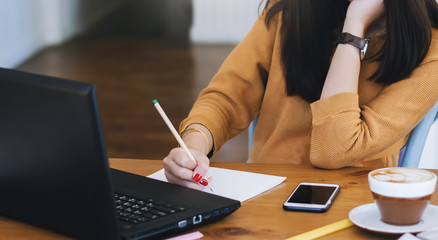 Young asian woman writing on paperwork while she working with laptop on desk