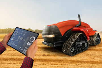 Wall Mural - Farmer with digital tablet controls autonomous tractor on a smart farm
