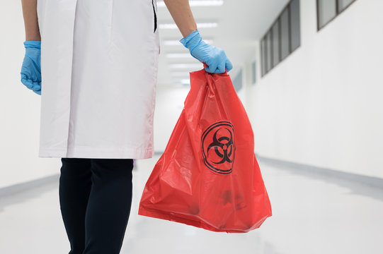 Scientist wearing blue gloves and red bag with bioharzard sign.A woman worker hand holding red garbage bag.Maid and infection waste bin at the indoor public building.Infectious control.