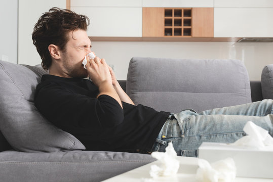 Sick man lying on sofa and blowing nose