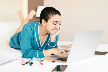 Smiling girl in dress using laptop on bed.
