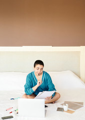 Thoughtful ethnic student reading notes on bed
