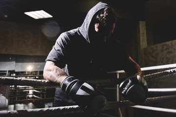 Closeup portrait of a professional boxer in a hood and gloves in the ring. Dark colors, face in shadow