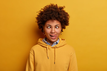 Fototapeta Photo of funny young woman has crazy face, crosses fingers and sticks out tongue, foolishes around, wears casual sweatshirt, poses against yellow background. Comic facial expressions concept obraz