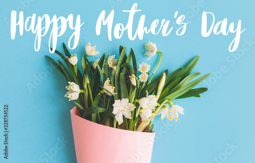 Happy Mother's day text on white spring flowers in pink bouquet on blue background. Stylish floral creative greeting card. Spring snowflake blooming flowers flat lay. Happy mothers day