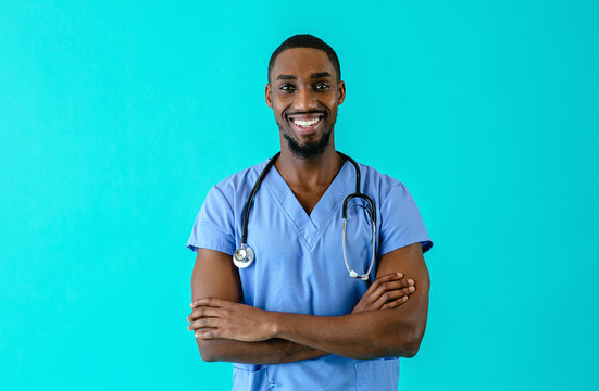 Portrait of a friendly male doctor or nurse wearing blue scrubs uniform and stethoscope, with arms crossed, isolated on blue studio background