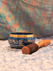 Blue and golden singing bowl made of seven metals with a wooden striker on an Indian scarf