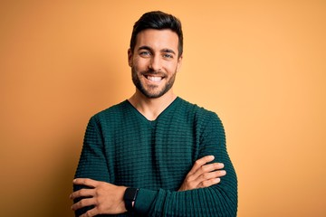 Young handsome man with beard wearing casual sweater standing over yellow background happy face...