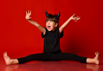 Kid with horns, in black blouse and leggings. Screaming, sitting on floor with arms and legs apart. Red background. Close up Wall mural