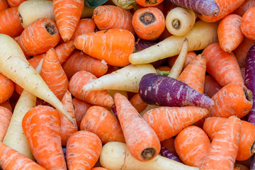 Pile of purple, orange and white Chantenay carrots, Daucus carota, on a market stall. Background image