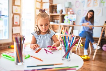 Caucasian girl kid playing and learning at playschool with female teacher. Mother and daughter at playroom around toys drawing with pencil colors