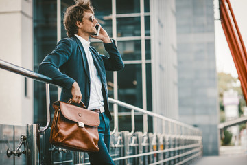 Elegant young businessman talking on mobile phone while standing outside airport, experienced male employer using cell telephone while waiting for taxi car outdoors before work