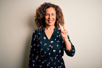Wall Mural - Middle age beautiful woman wearing casual dress standing over isolated white background smiling with happy face winking at the camera doing victory sign. Number two.