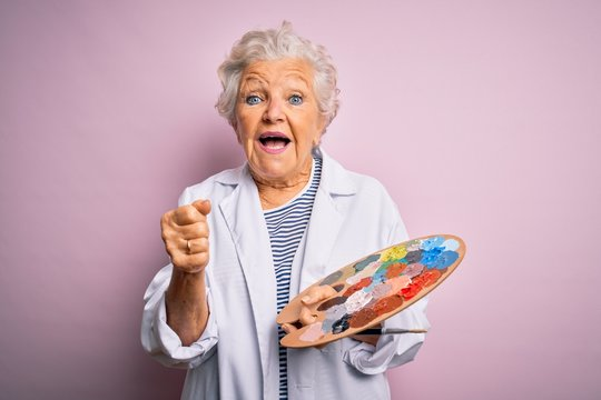 Senior beautiful grey-haired artist woman painting using brush and palette over pink background screaming proud and celebrating victory and success very excited, cheering emotion