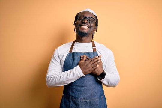 Young african american cooker man wearing apron and over isolated yellow background smiling with hands on chest with closed eyes and grateful gesture on face. Health concept.