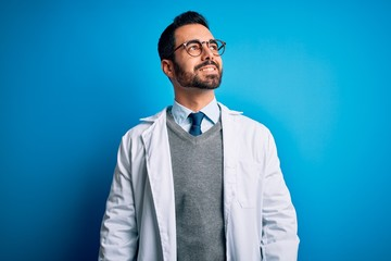 Young handsome doctor man with beard wearing coat and glasses over blue background looking away to...