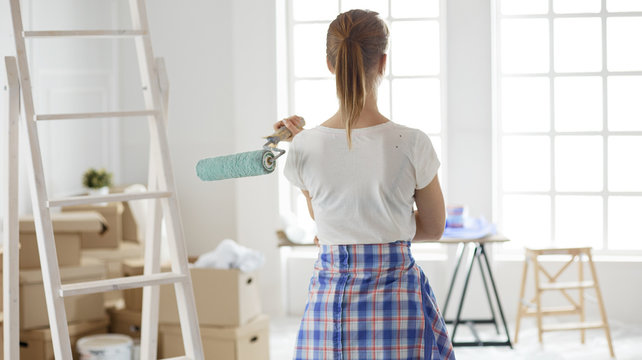 Pretty smilling woman painting interior wall of home with paint roller