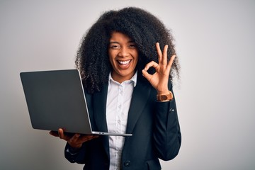 Young african american business woman with afro hair using computer laptop from job doing ok sign with fingers, excellent symbol