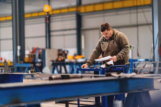 Industrial worker looking at blueprint