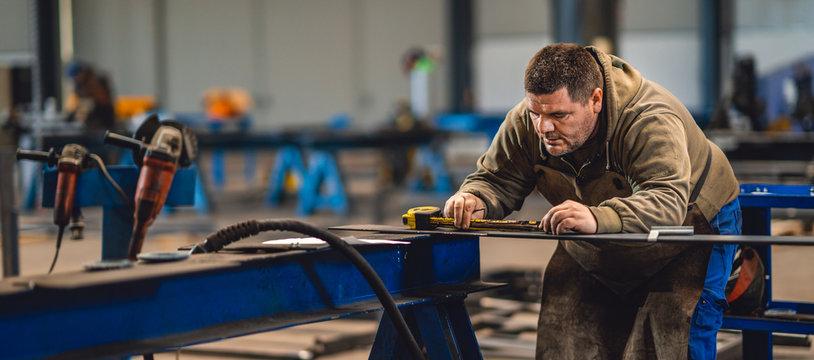 Industrial worker measuring the steel plate