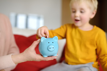 Mother and child putting coin into piggy bank. Education of children in financial literacy
