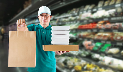 Delivery service ingredients food for order online shopping and icon media symbol. Delivery man in green uniform hand holding paper box and bag package for grocery express service concept.