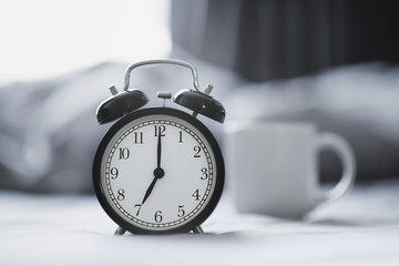 Closeup - Alarm clock have a good day with a cup of coffee on the bed background in the morning sunlight. Fotomurales