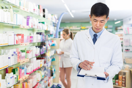 Chinese man is attentively looking medicine with notebook