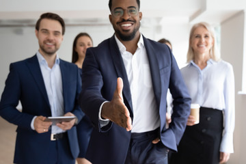 Group portrait of smiling multiracial businesspeople greeting newcomer to successful team, happy African American businessman stretch hand get acquainted with job applicant, recruitment concept