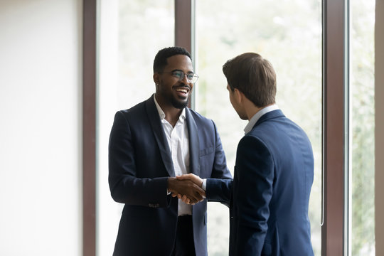 Overjoyed multiethnic businessmen shake hands greeting getting acquainted in office, smiling diverse multiracial male business partners handshake close deal make agreement after successful negotiation