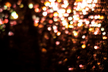 Bokeh blurred abstract lights colored on black glitter shiny sparkle background