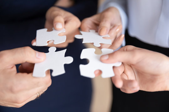 Close up of diverse businesspeople assemble jigsaw puzzle find business solution together, hands of multiracial people colleague put pieces together engaged in teambuilding activity, teamwork concept