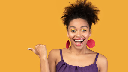 Excited black woman pointing finger at free space