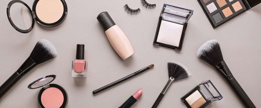 Flat lay with set of professional decorative cosmetics, makeup tools and woman accessories over gray background with copy space. Beauty blog, fashion, party and shopping concept