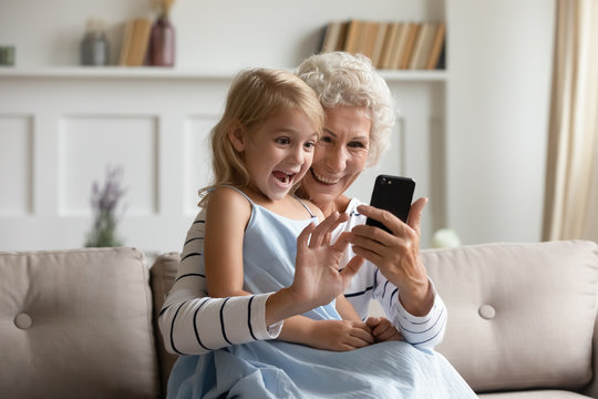 Overjoyed mature grandmother and cute little granddaughter sit on couch relax using smartphone together, happy senior granny and small grandchild have fun watch funny videos on modern cellphone