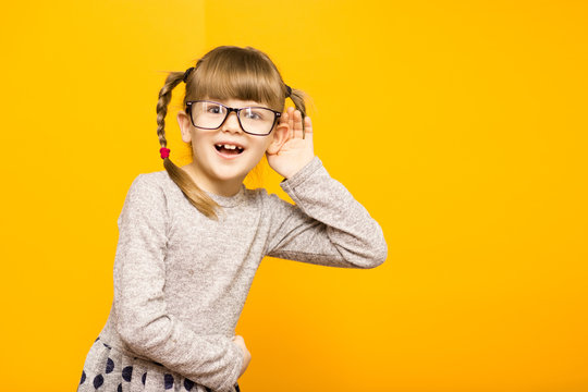 Little child girl journalist in glasses with surprised euphoria face and funny pigtails listening to something holding his hand to ear