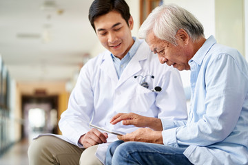 young asian doctor talking to senior man in hospital hallway