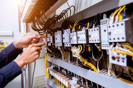 Electrician measurements with multimeter testing current electric in control panel.