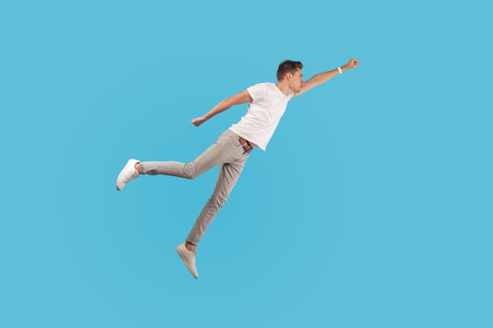 Full length portrait of motivated confident man in white t-shirt and casual pants flying up in air as superhero with raised hand, feeling superpower. indoor studio shot isolated on blue background