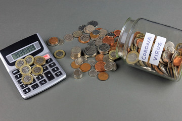 Pound coins resting on top of a calculator. Calculating the costs of the coronavirus to the economy concept.