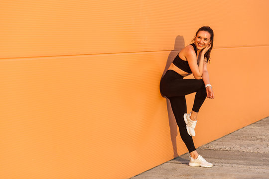 Attractive sexy girl with fit body in tight sportswear, black pants and top, leaning against orange wall and smiling to camera, living healthy sport life, full of energy. isolated on advertising area