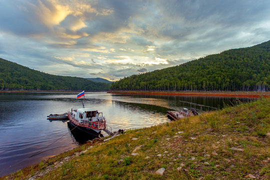 Beautiful landscape. Zeya reservoir, Amur region. A small boat moored at the reserved shore against the backdrop of a beautiful sunset. Reflection of sunset in the water.