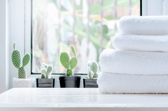 Clean towel on white table near window sill.