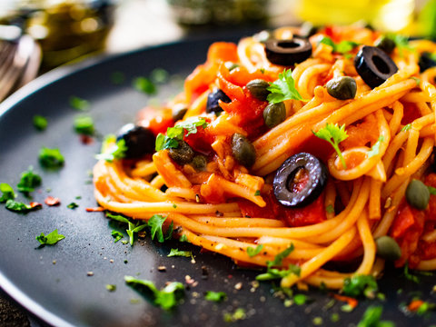 Pasta puttanesca with tomato sauce, anchovies, chilli, capers and olives on wooden table