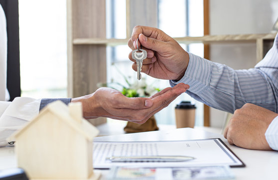 The sales manager or real estate sales representative handed the keys to the customer after signing the contract, signing the lease or buying a house with home loan and home insurance offers