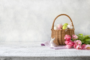 Wicker basket with easter eggs and pink tulips. Spring easter background with space for text. Close up.